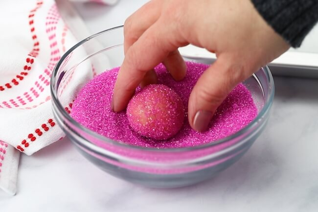 dipping pink cookie ball into magenta sprinkles