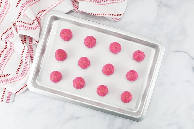 pink champagne cookie dough balls on baking sheet