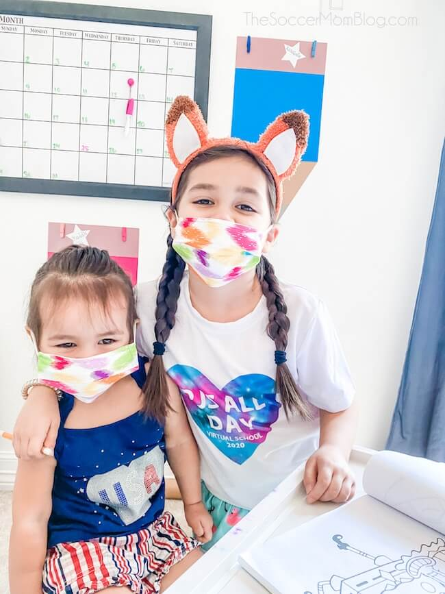 two little girls wearing cloth face masks