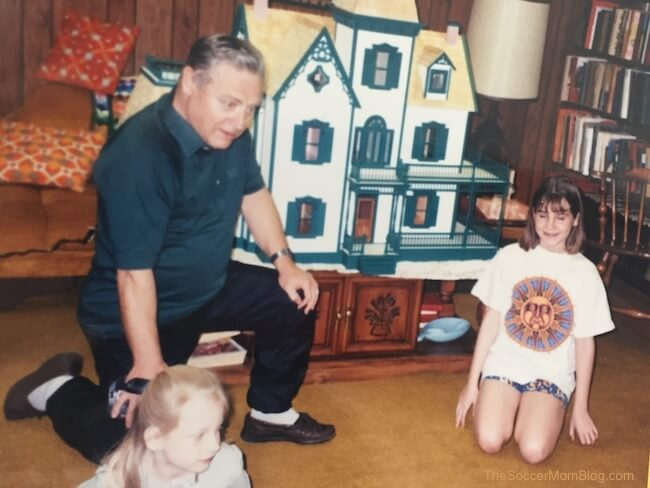 Grandpa and granddaughters playing with a dollhouse