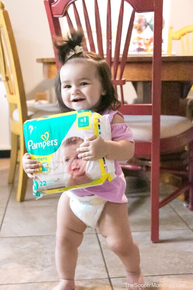smiling baby girl holding pack of Pampers