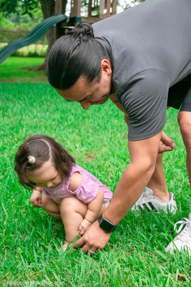 dad and baby daughter playing in the grass