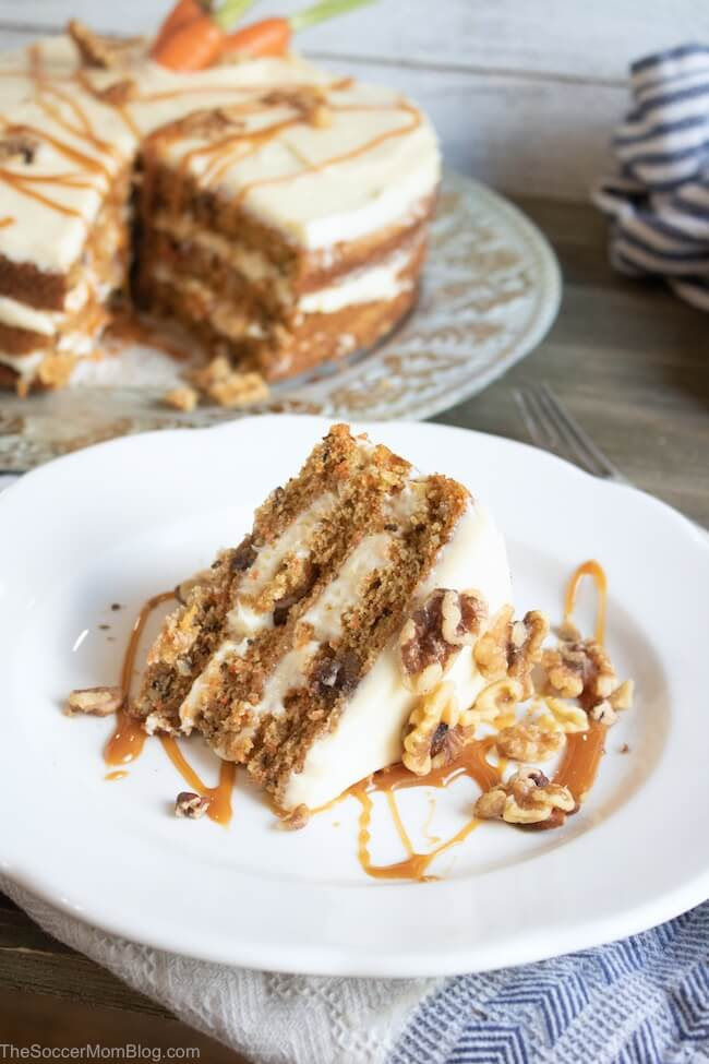 wide shot of a slice of carrot cake on a white plate with cake in background