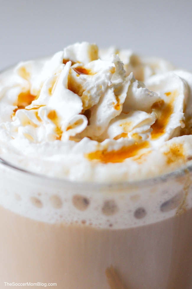 close up of whipped cream with caramel sauce on a latte