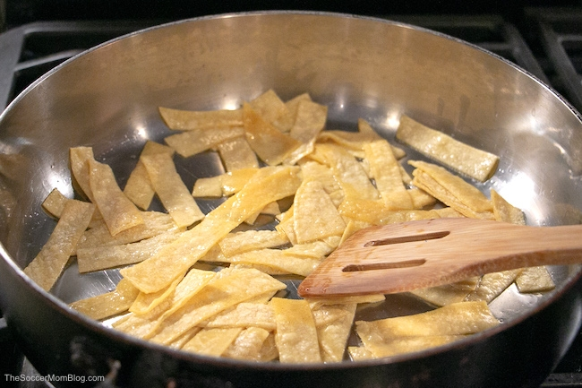 frying tortilla strips to make migas