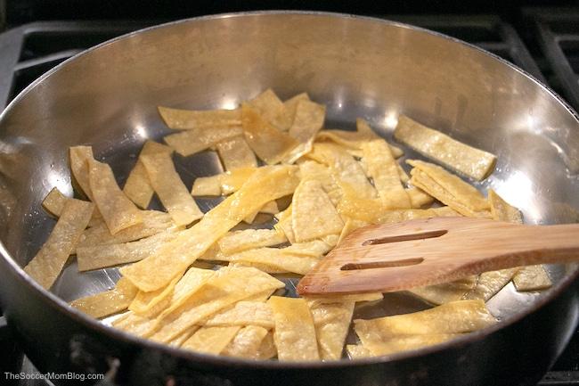 frying tortilla strips to make migas