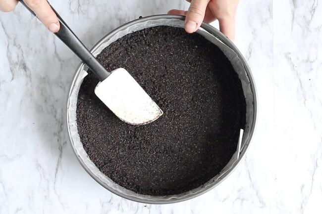 pressing oreo crust into springform pan