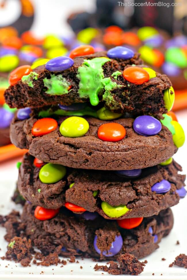 stack of chocolate cookies with Halloween M&Ms and green frosting filling