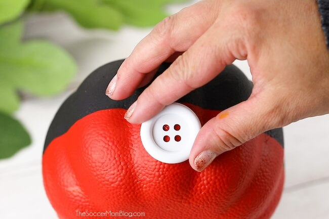 putting white buttons on a Mickey Mouse pumpkin