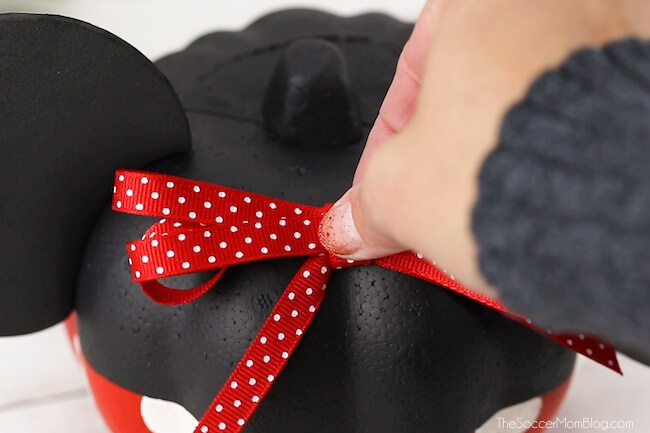 attaching bow to Minnie Mouse pumpkin