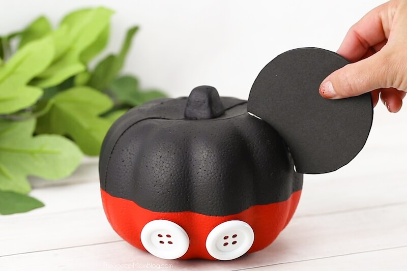 attaching ouse ears to Mickey Mouse pumpkin