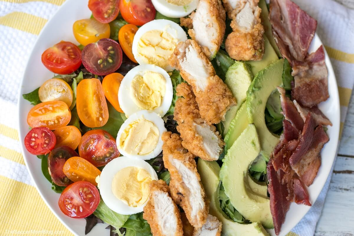 close up of a crispy chicken Cobb salad on white plate