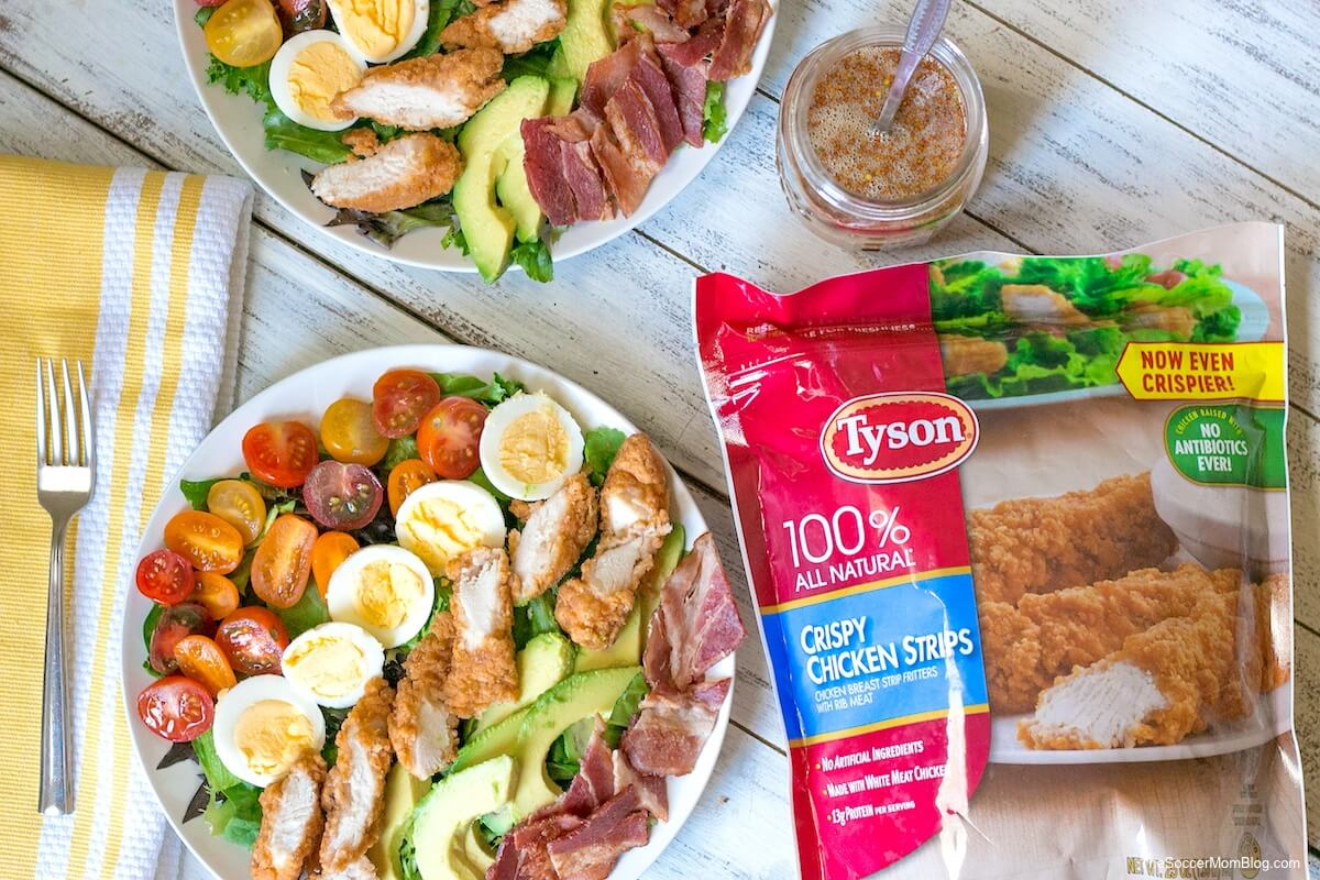 crispy chicken Cobb salad plated next to a bag of Tyson Crispy Chicken Strips