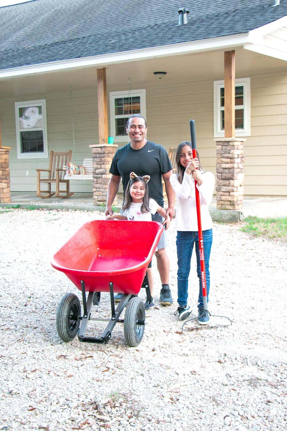 family with wheelbarrow in front of house