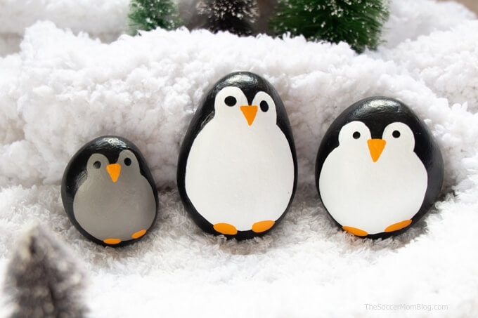 a family of penguin painted rocks in fake snow