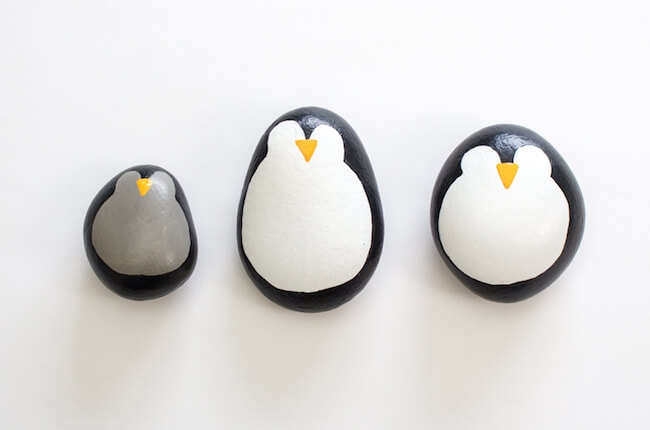 three painted rocks made to look like penguins