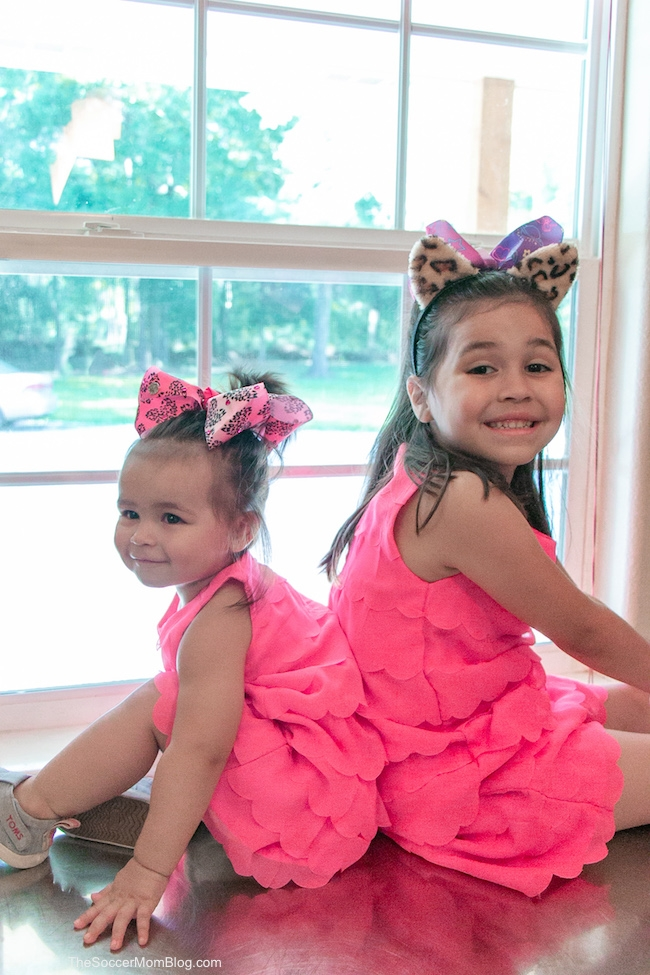 two little girls in pink dresses sitting in front of a window
