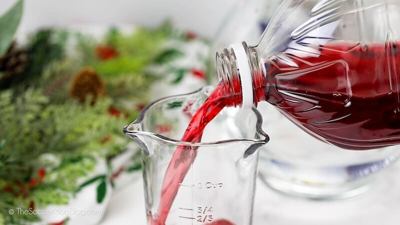 pouring cranberry juice into measuring cup