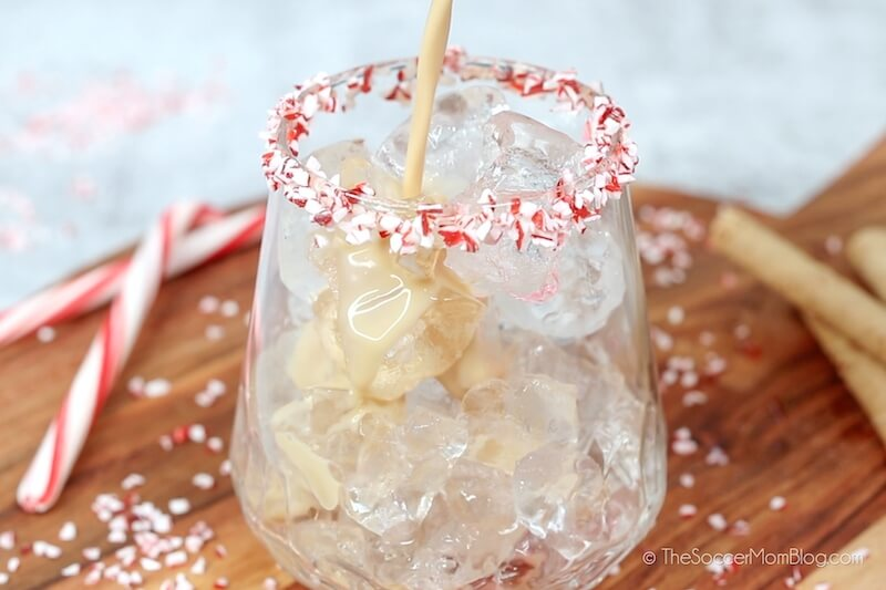 pouring peppermint mocha cocktail into glass with crushed candy canes