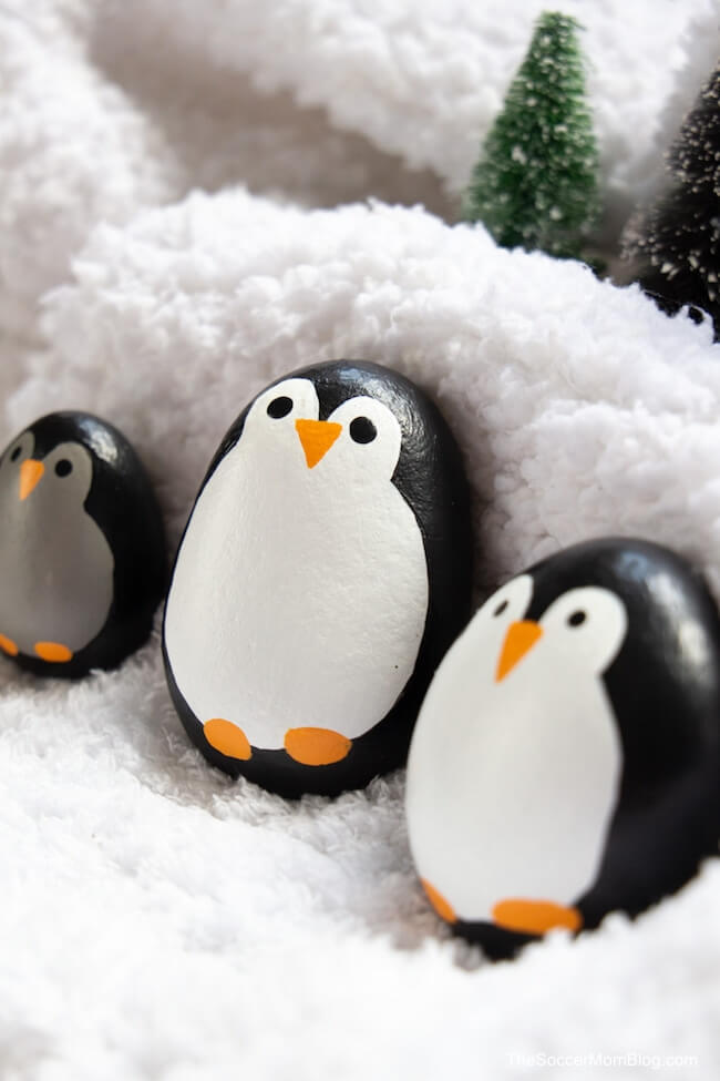 family of penguin painted rocks in fake snow