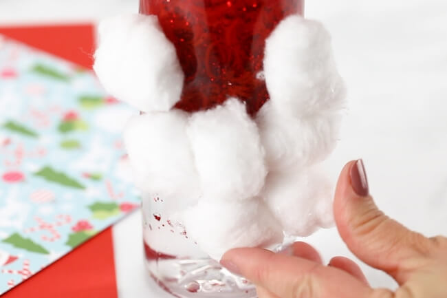 Gluing cotton balls to Christmas sensory bottles