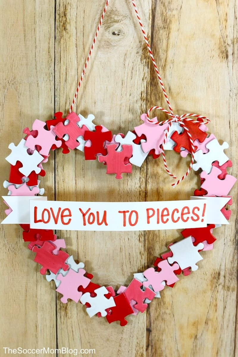 This adorable DIY Valentine Wreath is an easy and thrifty Valentine's Day craft to make with kids. All you need is a dollar store puzzle, a recycled cardboard box, and simple art supplies!