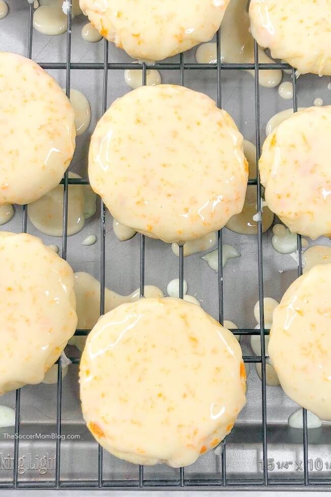 iced orange cookies drying on baking rack
