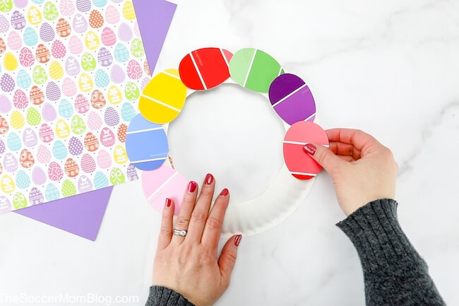 attaching paint strips to paper plate Easter wreath