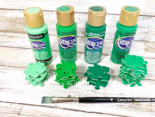 painting green puzzle pieces for a St. Patrick's Day wreath