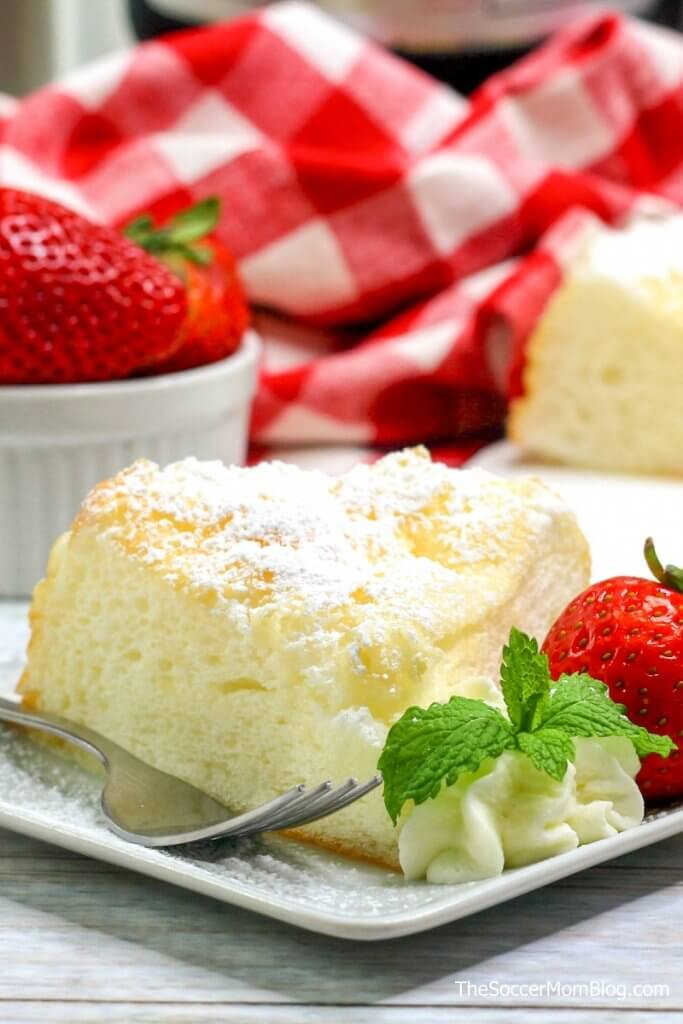 a slice of angel food cake with strawberries and powdered sugar