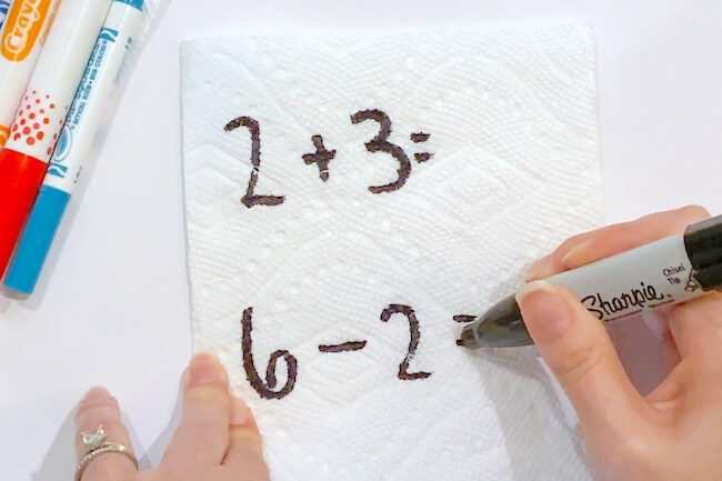 writing math problems on paper towel with permanent marker