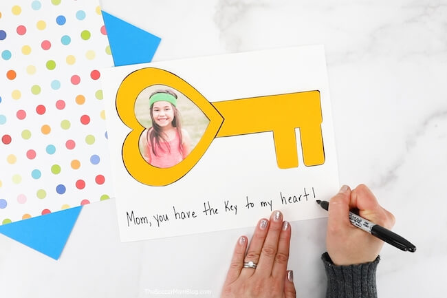 "writing ""Mom, you have the key to my heart"" on card"