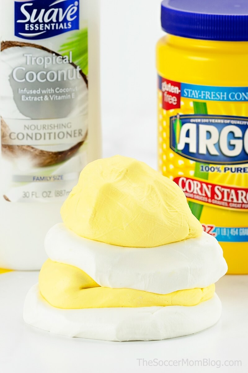 blobs of white and yellow cloud dough with conditioner bottle and cornstarch container