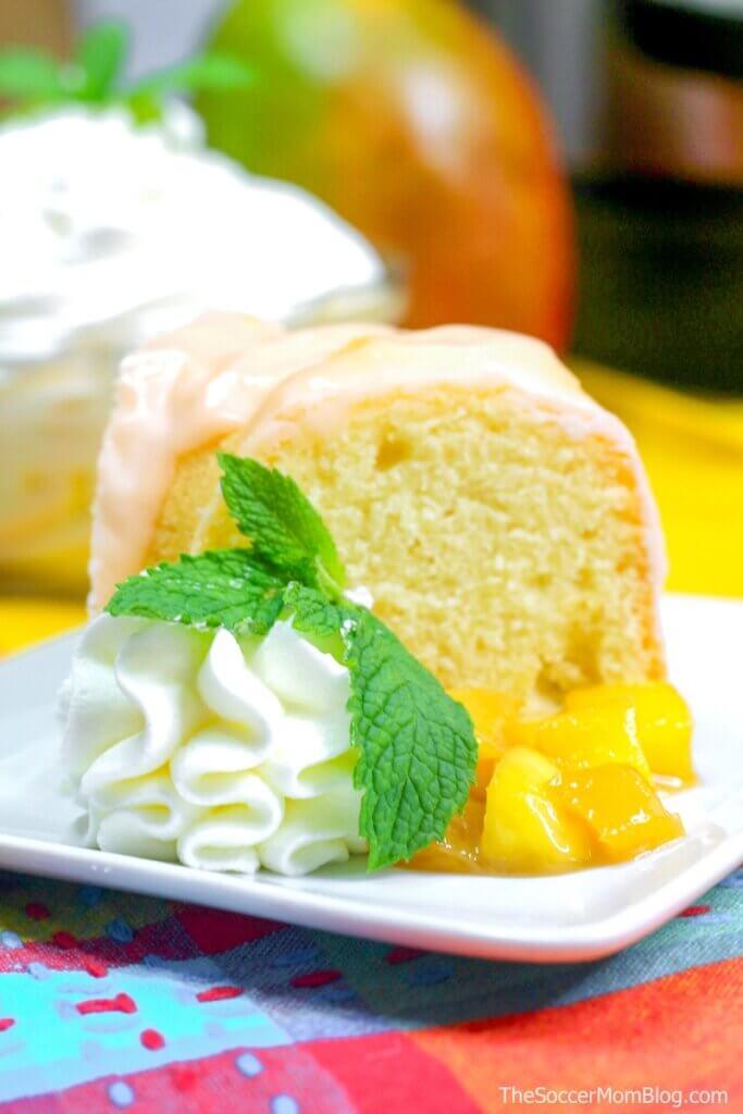 slice of mango coconut bundt cake with fresh mangos and whipped cream