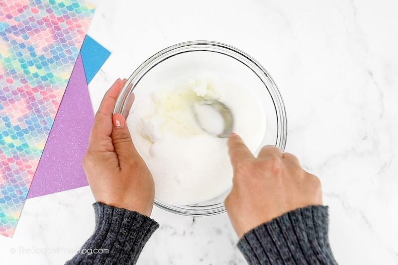 mixing sugar and coconut oil to make sugar scrub