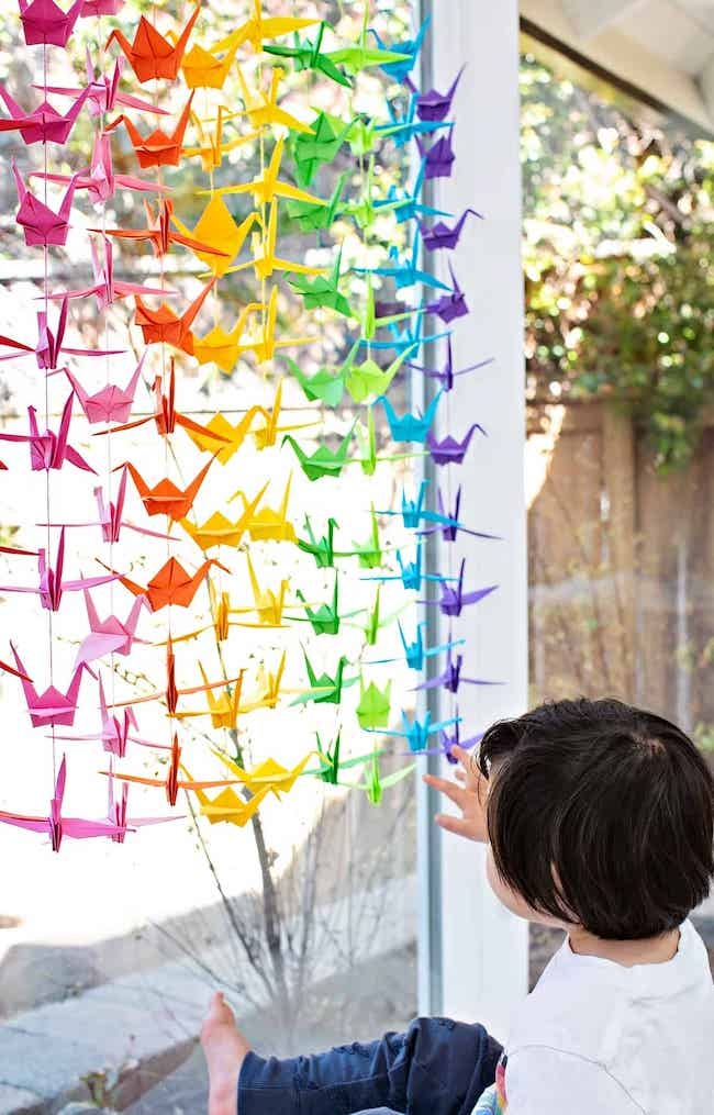 colorful paper origami cranes hanging in window