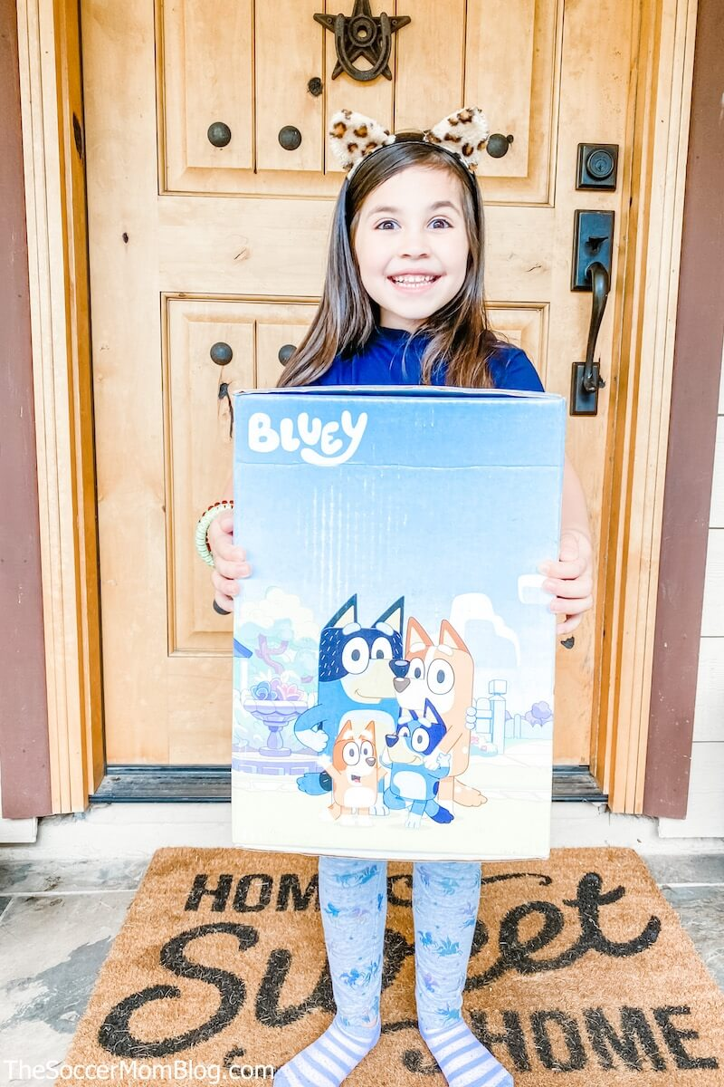 little girl holding box with Bluey character on it