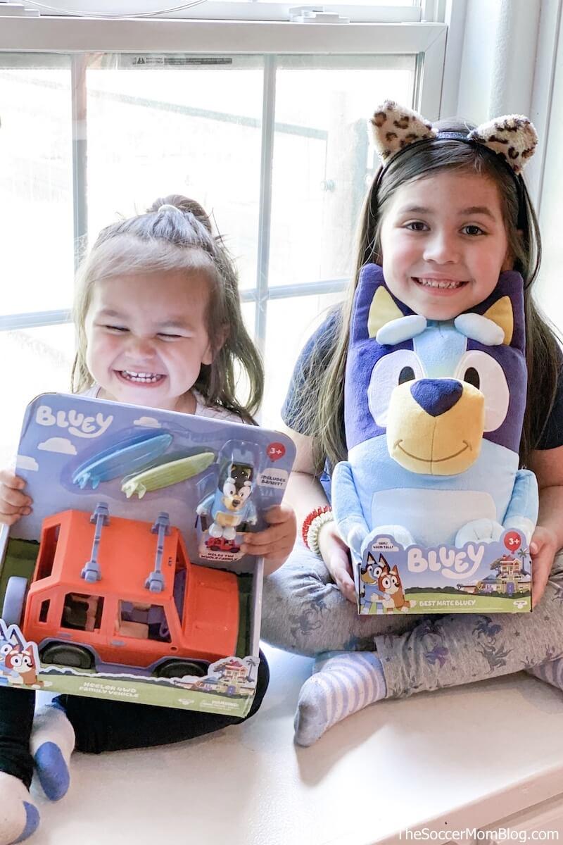 little girls holding Bluey toys