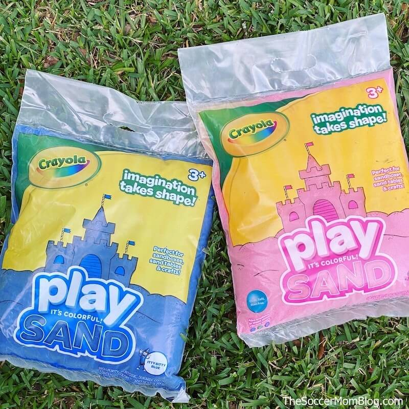bags of Crayola play sand laying in grass