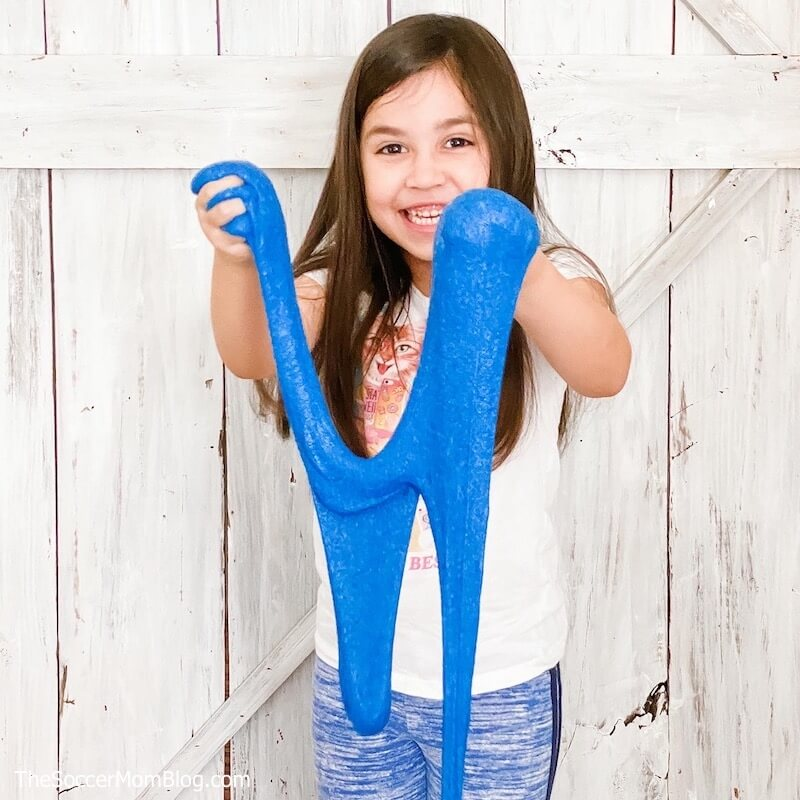 little girl playing with blue kinetic sand slime