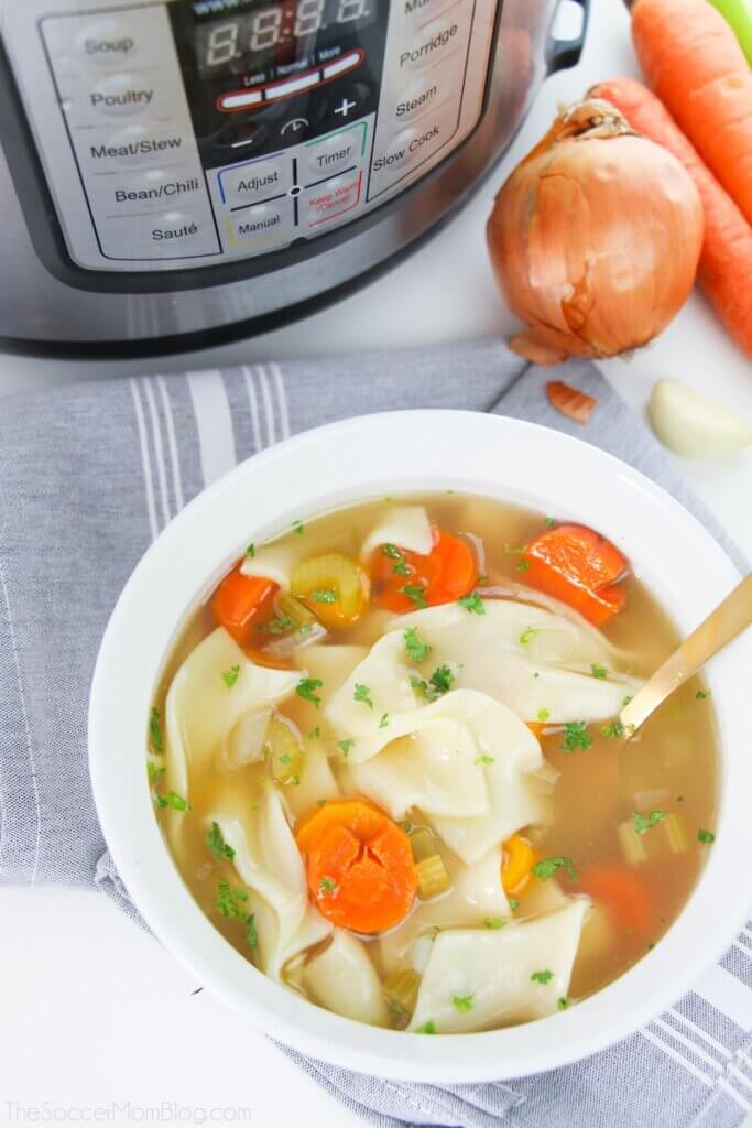 bowl of homemade chicken noodle soup with Instant Pot in background
