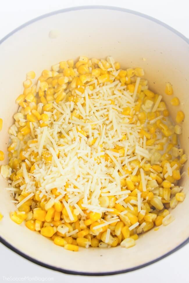 adding shredded parmesan cheese to corn in pot
