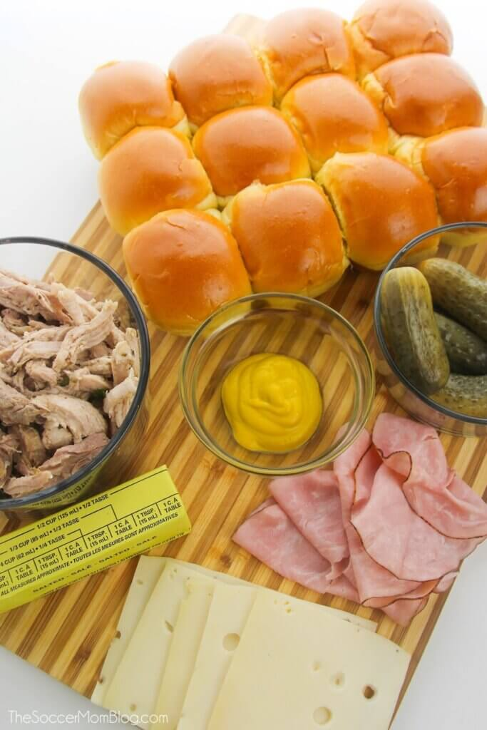 ingredients needed to make Cuban sliders, on a wooden cutting board