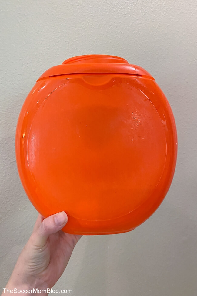 holding up an empty orange Tide laundry pods container