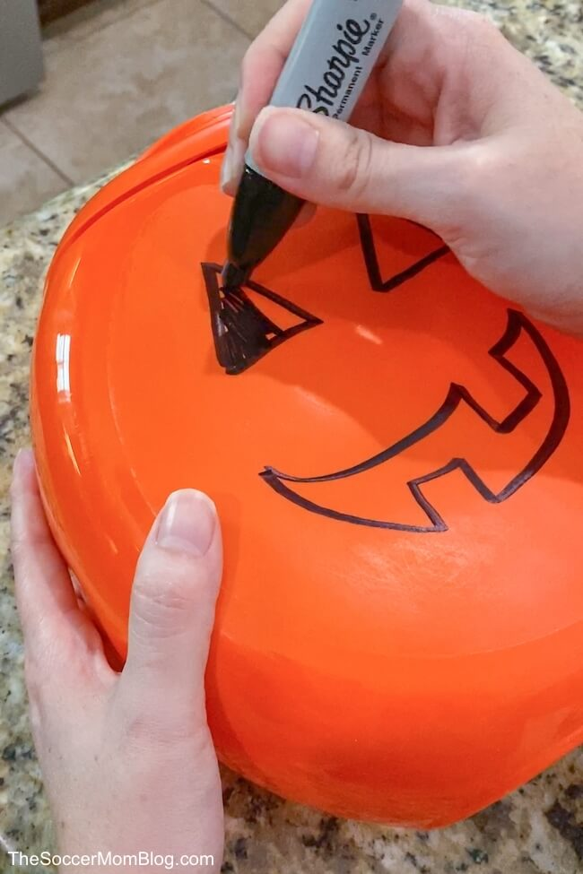 drawing a Jack-O-Lantern on an empty laundry container