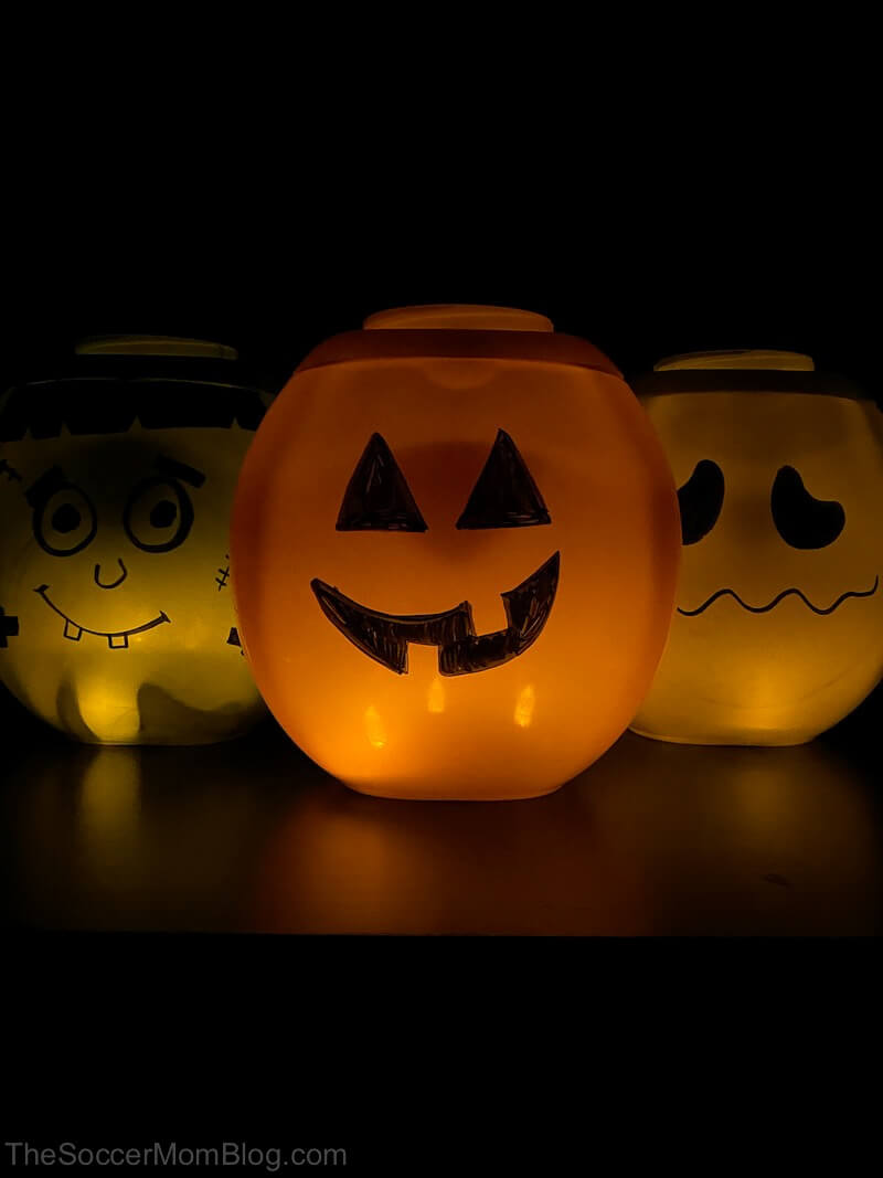 glowing DIY jack-o-lanterns made out of laundry detergent containers