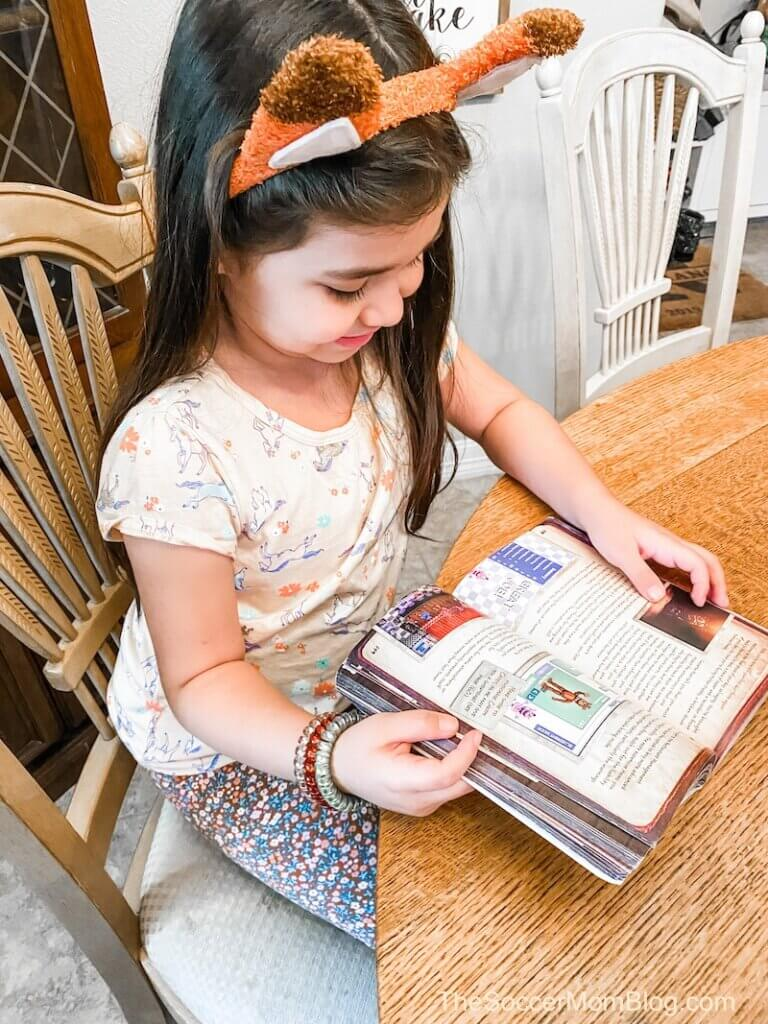 little girl reading book at table