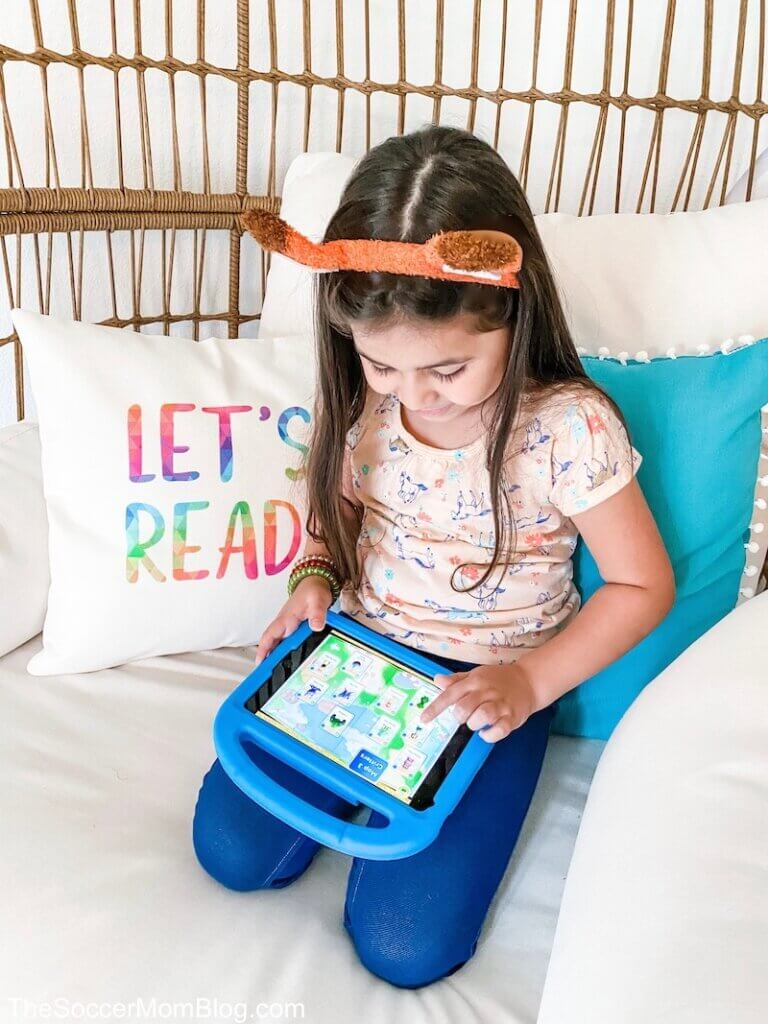 little girl playing Reading Eggs app on tablet