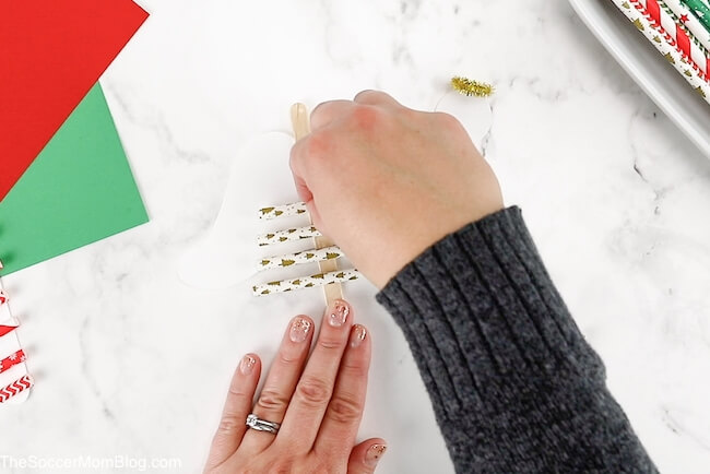 gluing gold straws on angel Christmas ornament