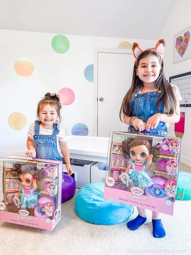 two girls holding Baby Born dolls